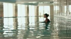 Beautiful girl in bikini swimming in the indoor pool - stock footage