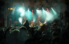 Stock Photo of Rock concert, silhouettes of happy people raising up hands