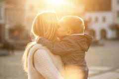 Happiness mother and son on the street at sunny day. Stock Photos