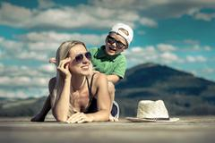 Happiness mother and son on the pier at sunny day under sunlight - stock photo