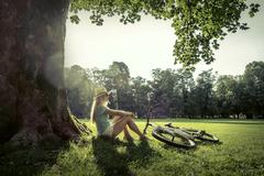 Woman sitting under sun light at day near her bicycle in the par - stock photo