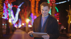 The young man walks on the evening city and reads news on the tablet - stock footage