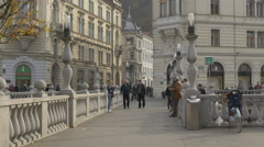 People walking, chatting and relaxing on the Triple Bridge in Ljubljana Stock Footage