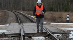 Railroad worker with documentation and adjustable wrench walking on railway Stock Footage
