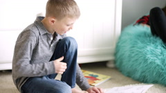 Little boy sitting on the floor at home reading an origami book Stock Footage