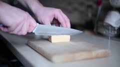 Man cuts the cheese on board close up Stock Footage
