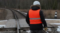 Railroad worker with documentation and adjustable wrench cross railway crossing - stock footage