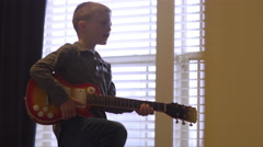 Little boy playing around with an electric guitar at home Stock Footage