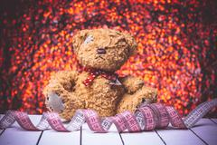 Teddy bear sitting on white wooden floor. Nice bokeh background with centimeter Stock Photos