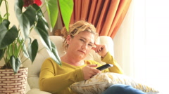 Sleepiness, yawning woman on the couch with TV remote control - stock footage