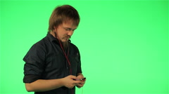 Man listening to music on the phone on a green screen Arkistovideo