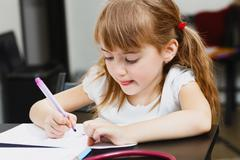 Cute preschooler girl drawing with felt-tip pens Stock Photos