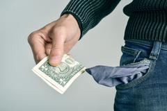 man with only one US dollar in his pocket - stock photo