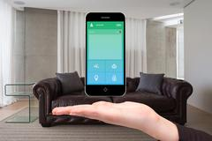 Hand showing home automation on phone Stock Photos