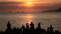 Silhouetted young people watching  sunset Ipanema Beach, Rio de Janeiro, Brazil Stock Footage