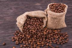 Coffee grains in bags with the scattered grains close up Stock Photos