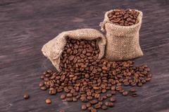 Two bags with coffee and the scattered grains on a dark wooden board - stock photo