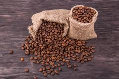Two bags with coffee and the scattered grains Stock Photos