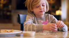 A little girl eating crackers at the kitchen counter, with bokeh behind her Stock Footage
