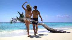 A loving couple enjoying vacation on a tropical beach. Slow motion Arkistovideo