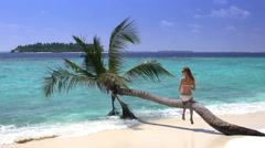 Beautiful slim young woman enjoying vacation on a tropical beach. Slow motion. - stock footage