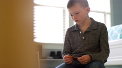 A little boy folds origami at home, door frame in the foreground Stock Footage