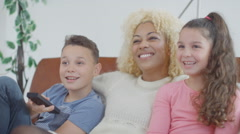 4K Happy mother & children watching TV on the couch at home - stock footage