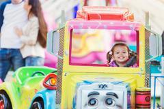 Little girl enjoying fun fair ride, amusement park Kuvituskuvat