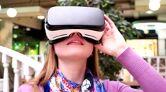 Smiling girl looks through VR glasses online presentation with virtual realit. Stock Footage