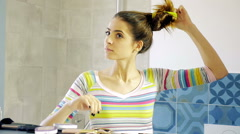 Happy beautiful young woman in front of mirror undoing ponytail slow motion - stock footage