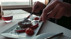 The man with a knife cuts the steak on a plate Stock Footage