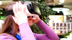 Girl wears Oculus and is immersed in the world of virtual reality. Stock Footage