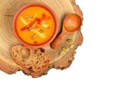 Bowl of pumpkin soup on wood cut over white - stock photo