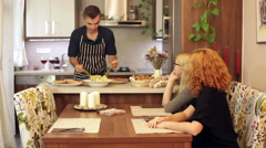 Young man serving vegetable salad for two women at home Stock Footage