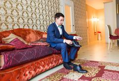 Groom is wearing shoes indoors. Male portrait of handsome guy. Beautiful model Stock Photos