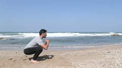 Side view on squat exercise on the beach Arkistovideo