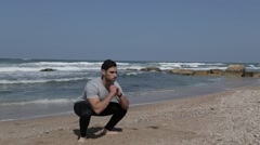 Man doing squat exercise on the beach - stock footage