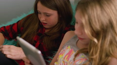 Preteen friends using their tablets together at home Stock Footage