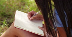 Mixed Race Person sitting at tree writing in journal - stock footage