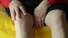 Close-up of an Old Woman Massaging Her Knee on the Couch Stock Footage
