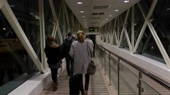 POV camera, passengers go through glass walled boarding bridge, night time Stock Footage