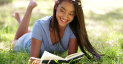 Mixed Race Person laying down outside reading a book Stock Footage