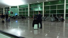 Small number of passengers at departure hall of airport, early morning Stock Footage
