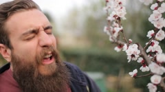 Young bearded man sniffing a flower, then sneeze - stock footage