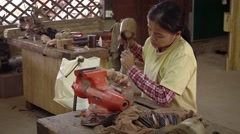 Local woman carves elephant from wood using traditional tools. Video 3840x216 Stock Footage