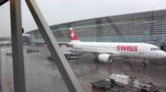 Airliner at Zurich Airport, from glass walled jet bridge, glide camera motion. Stock Footage