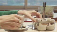 The female fills sugar in coffee and stirs Stock Footage