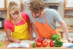 Couple cooking in kitchen reading cookbook Stock Photos