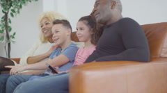 4K Happy laughing family watching TV on the couch at home - stock footage
