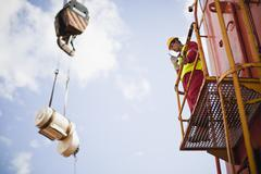 Worker directing crane on oil rig Stock Photos